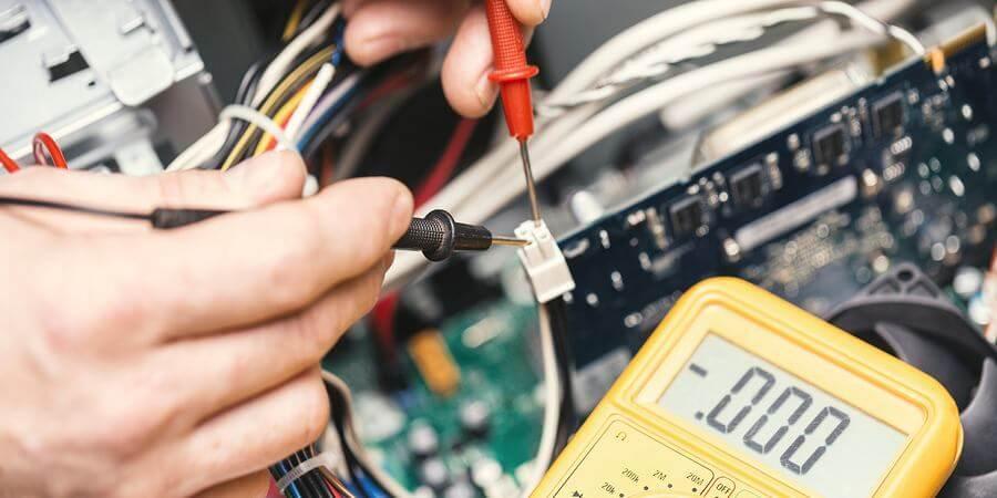 Technician hands with voltmeter above computer motherboard.