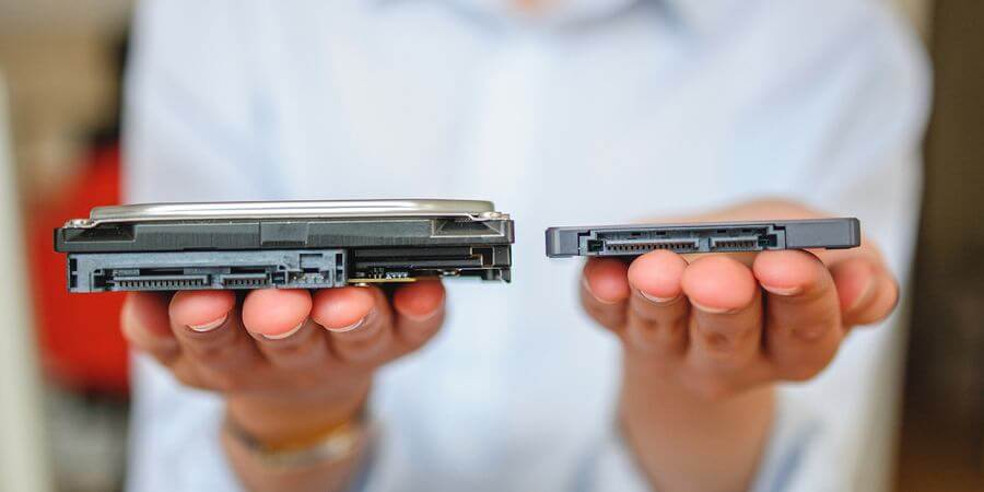 Hands holding Solid State Drive and Hard Drive Disk HDD