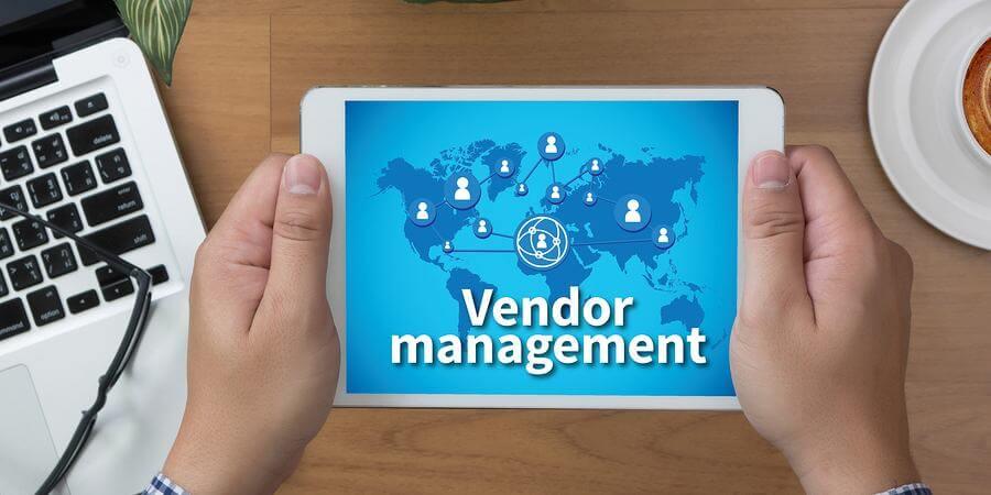 Vendor management on tablet held by a businessman.