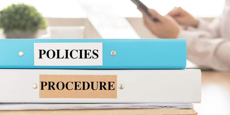 Policies and procedures documents placed on desk in meeting room.