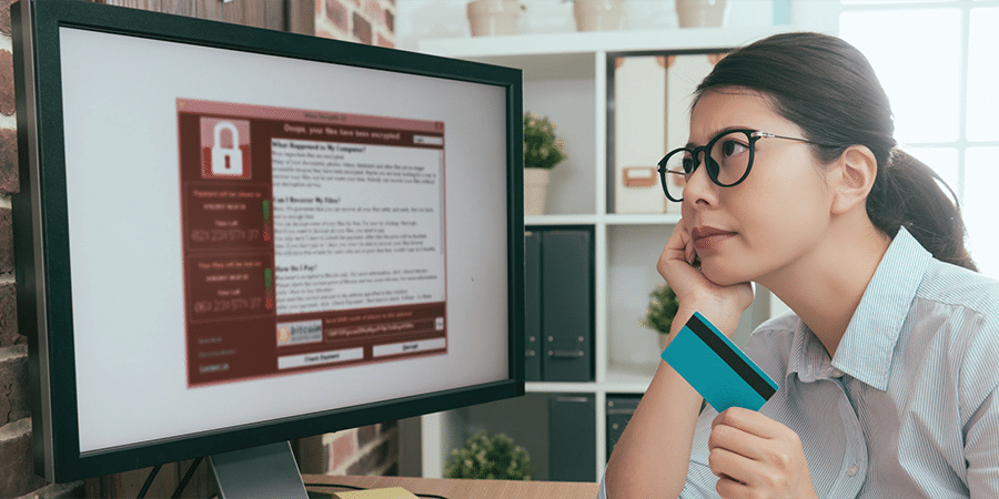 Business women holding credit card looking at computer screen with ransomware notice.